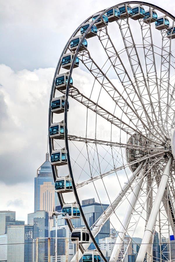 Ferris Wheel at Central Pier Overlooking Hong Kong Victoria Harbor. HDR rendering of Hong Kong skyline at downtown Central Pier with ferris wheel overlooking royalty free stock photo