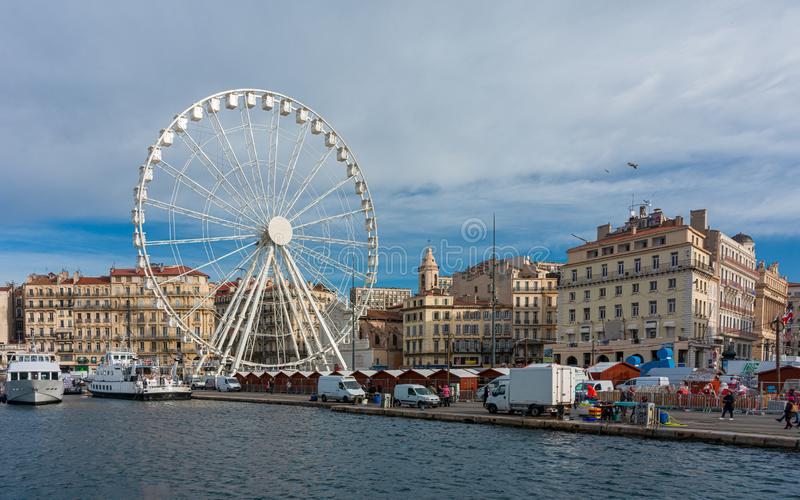 Marseille: The ferris wheel of the old port. The ferris wheel, the Christmas market barracks and the fish market on the old port of Marseille royalty free stock photography