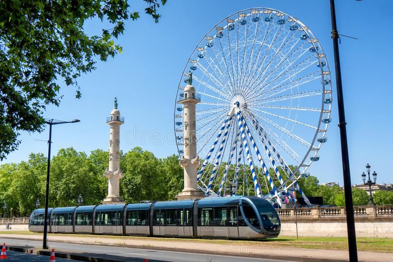 Ferris wheel in the city of Bordeaux in France with streetcar royalty free stock image