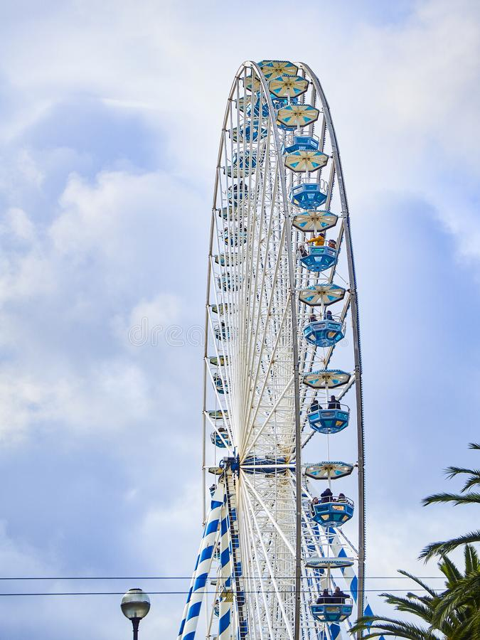 Ferris wheel with a cloudy sky in the background. San Sebastian, Spain - January 20, 2019. People enjoying of a Ferris wheel with a cloudy sky in the background royalty free stock image