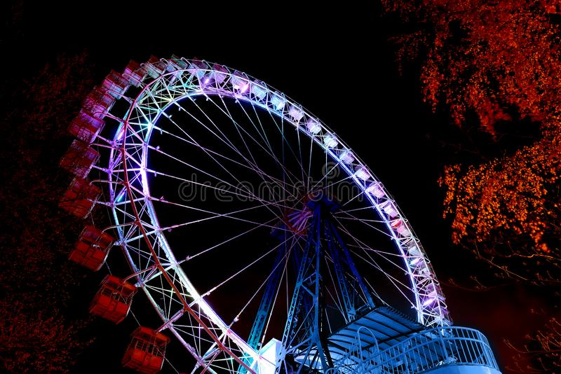 Ferris wheel with color lighting in funfair at night stock photography