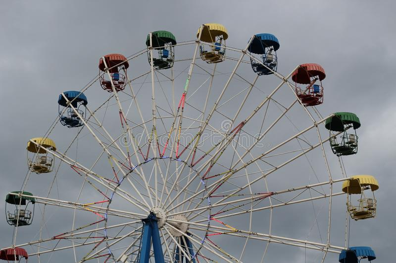Ferris wheel with colorful booths in the amusement Park on the background of the stormy sky.  royalty free stock photography