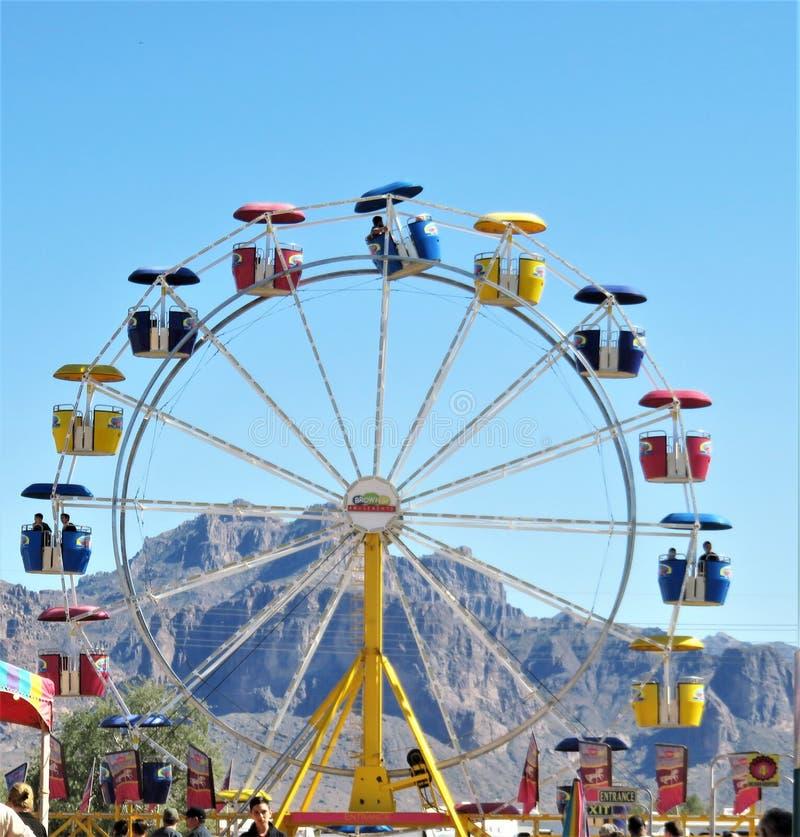 Ferris Wheel colorido contra el ajuste del cielo azul y de la montaña imágenes de archivo libres de regalías