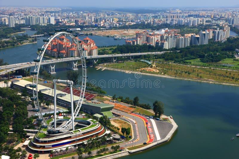 Ferris Wheel e un circuito di corsa a Marina Bay fotografia stock