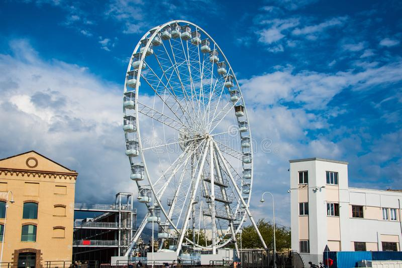 Ferris wheel in Genova, Italy with blue sky and white clouds royalty free stock photos
