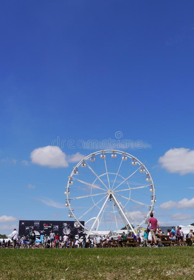 Ferris wheel and graduated blue sky at Goodwood Festival of Speed. UK. Low angle including grass, wheel people and sky royalty free stock photo