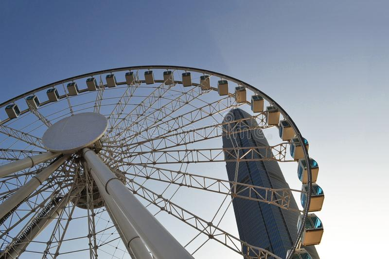 Ferris wheel in Hong Kong against a blue sky and a tall building royalty free stock images