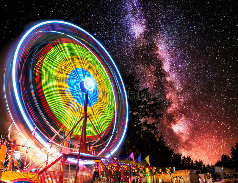 Ferris Wheel Light Motion Under Night Stars. A ferris wheel taken at night under the stars using a long exposure to capture the circular motion of the lights royalty free stock photography