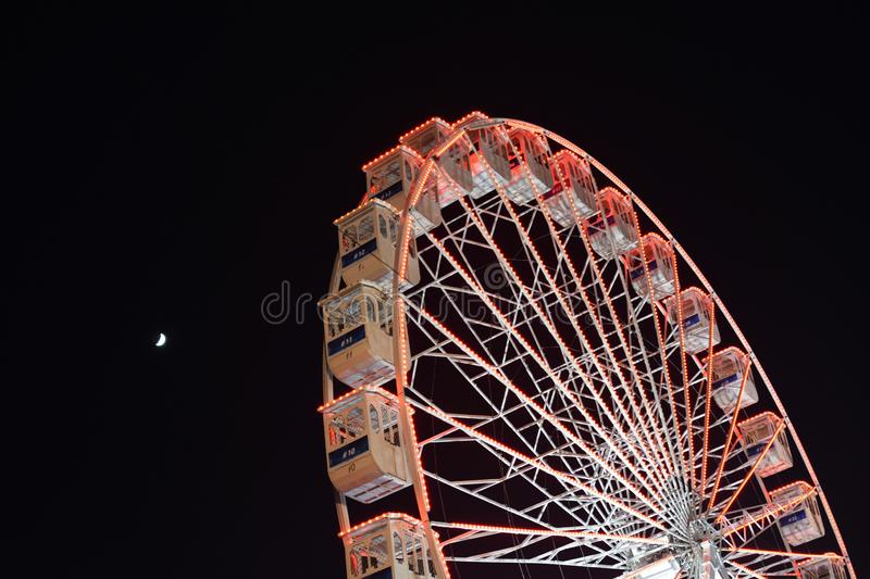 Ferris wheel and the moon. Black sky background. stock photography