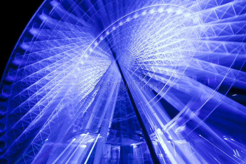 Ferris Wheel in motion glowing at night stock images