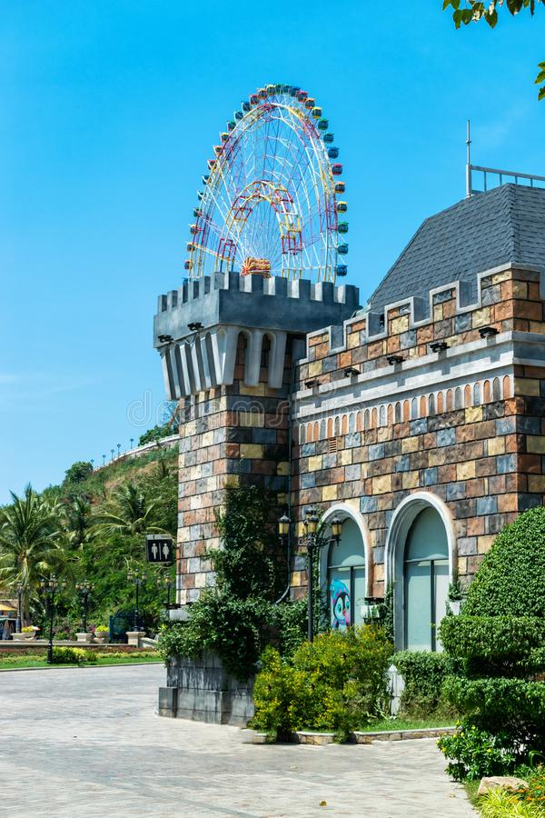 Ferris wheel over fairy castle with colorful walls in the amusement park stock photography
