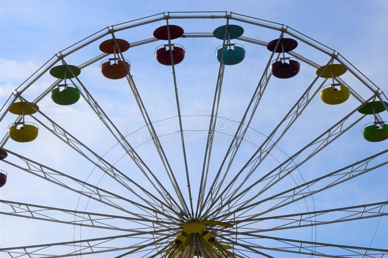 Big Rainbow car Ferris wheel in the blue sky. Ferris wheel with purple, blue, red, orange, green, and yellow cars in a cloudy blue sky stock images