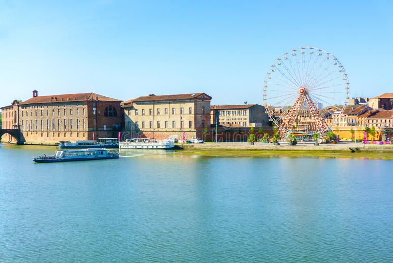 Ferris Wheel and view of Saint-Pierre Bridge over Garonne river and Dome de la Grave in Toulouse stock images
