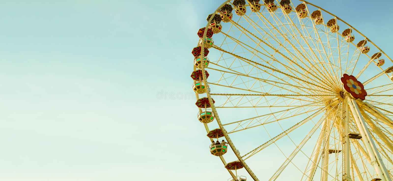 Ferris wheel or wonder wheel in an amusement park on a sunny summer day with blue sky and almost no clouds. royalty free stock photography