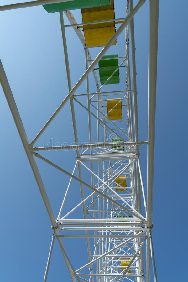 Ferris wheel with yellow and green booths against a blue sky stock photography