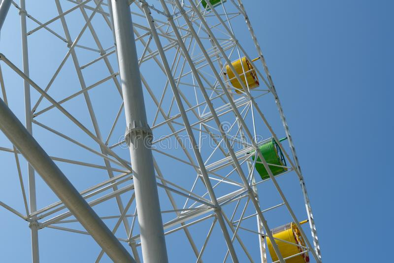 Ferris wheel with yellow and green booths against a blue sky. Attraction and entertainment, fair, fun, color, leisure, park, ride, holiday, travel, carnival royalty free stock images