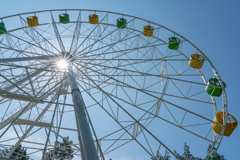 Ferris wheel with yellow and green booths against a blue sky. Attraction and entertainment, fair, fun, color, leisure, park, ride, holiday, travel, carnival stock photography