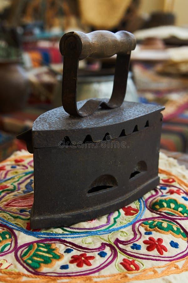 Ferro antigo de carvão, close-up Ferro fundido antigo na matéria têxtil colorida foto de stock royalty free