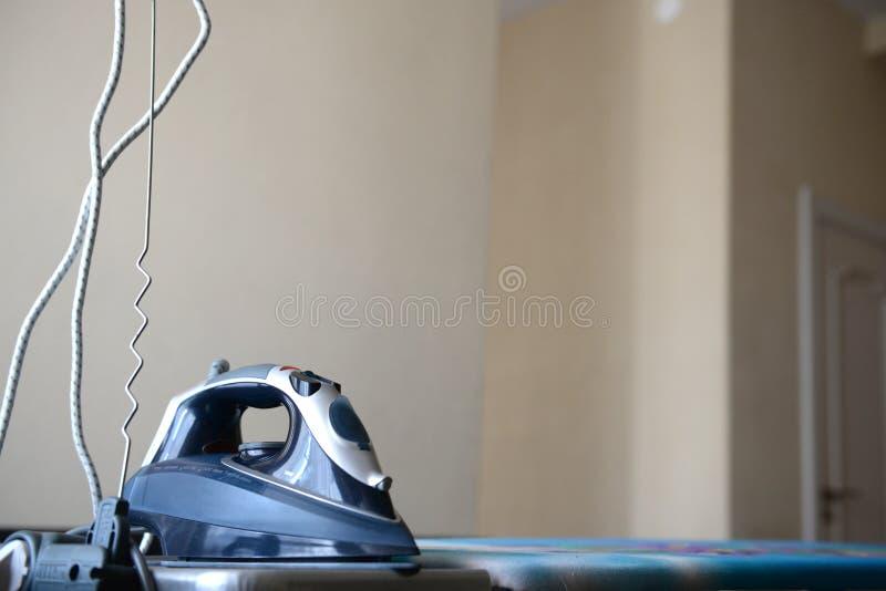 Ferro azul em uma tábua de passar a ferro fotografia de stock royalty free