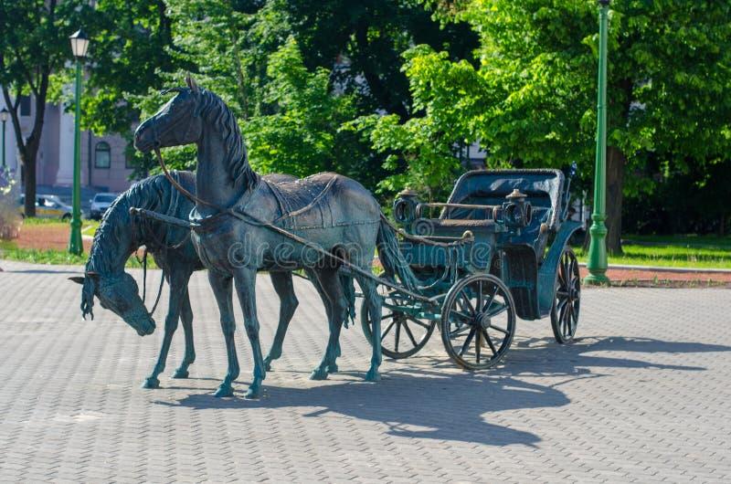 Ferro, cavalos de bronze com um transporte no parque fotos de stock