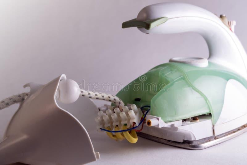 Ferro da stiro verde smontato La parte posteriore rimossa del dispositivo elettrico con accesso a collegamenti elettrici Ripari d immagini stock libere da diritti