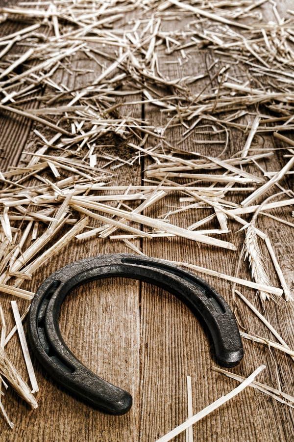 Ferro di cavallo rustico sul vecchio pavimento di legno del granaio con paglia fotografia stock