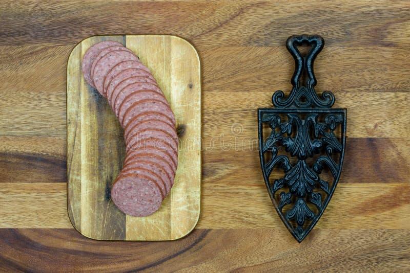 Ferro fundido e salsicha rústicos com fundo de madeira fotos de stock royalty free