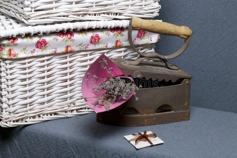 Ferro velho, aquecido por carvões quentes Encontrado perto do cestas de vime Um ramalhete de flores secadas é encaixado no ferro  imagem de stock
