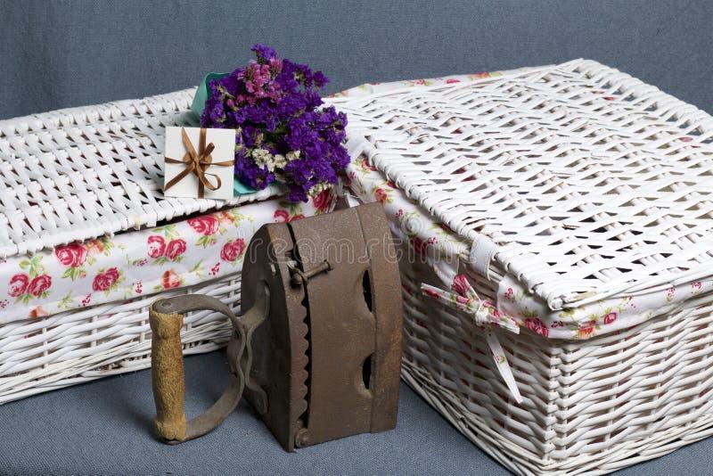 Ferro velho, aquecido por carvões quentes Localizado na tela cinzenta Estão próximo as cestas de vime, um ramalhete de flores sec foto de stock