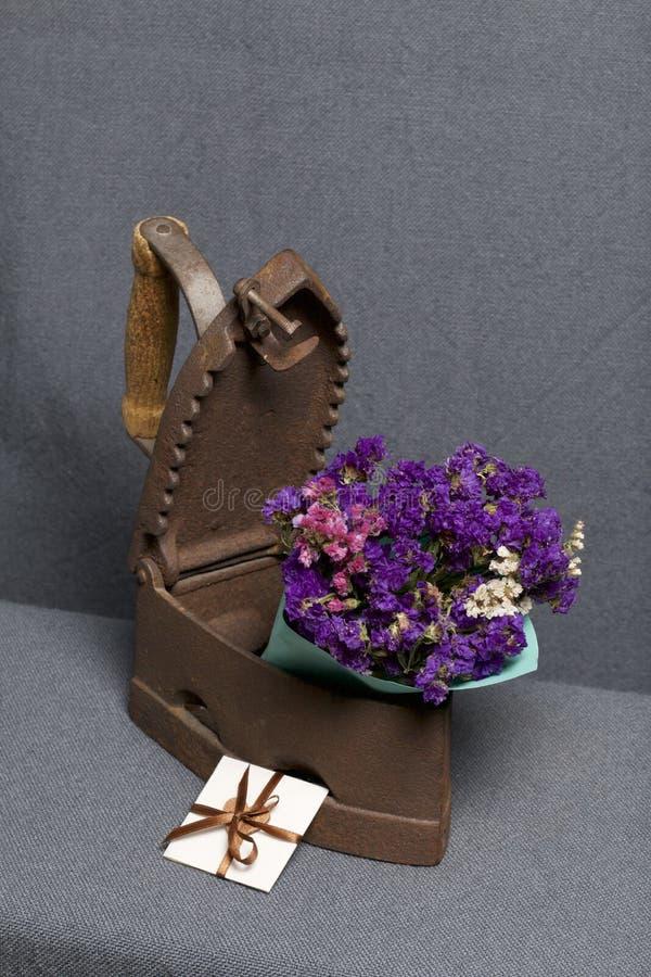 Ferro velho, aquecido por carvões quentes Um ramalhete de flores secadas é encaixado no ferro levemente aberto Está próximo um ca fotografia de stock