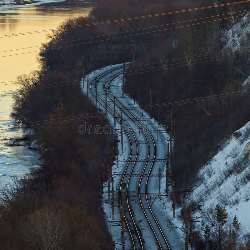 Ferrocarril en el área montañosa en la orilla del río imagenes de archivo