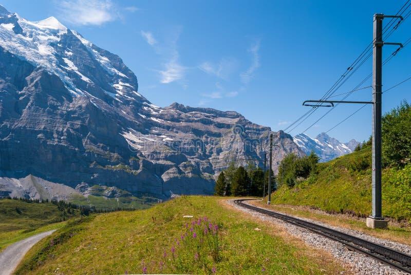 Ferrocarril en el fondo de la montaña de Jungfrau en las montañas de Suiza imagenes de archivo