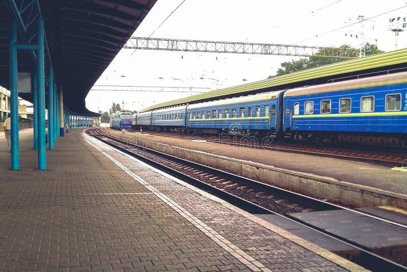 Ferrocarril en un día de verano nublado Plataforma de la trayectoria libre para los trenes de llegada El tren azul se coloca ante fotografía de archivo libre de regalías