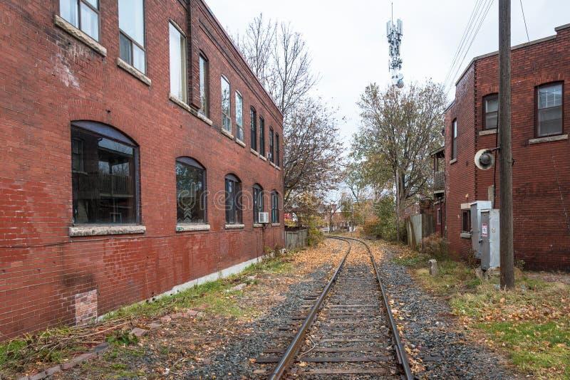 Ferrocarril entre dos el ladrillo Buldings en un día lluvioso fotos de archivo