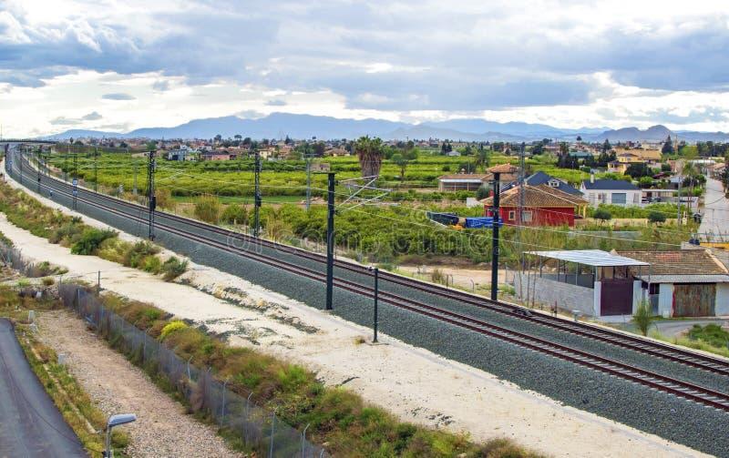 Ferrocarril que pasa por una pequeña ciudad en España foto de archivo