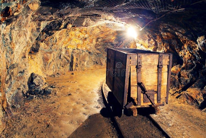 Ferrocarril subterráneo del túnel del oro de la mina foto de archivo