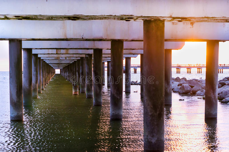 Ferroconcrete pillars of pier. Palanga, Lithuania. Ferroconcrete pillars of pedestrian seaside pier set in water on coast of Baltic sea. Sunset at Baltic sea in royalty free stock images