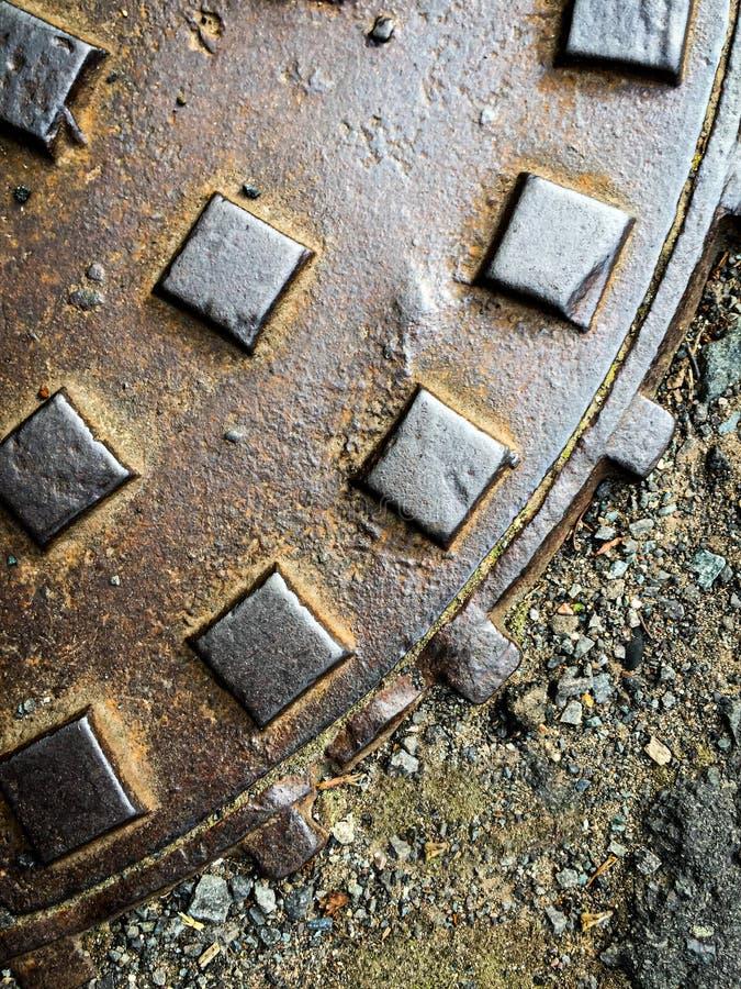 Ferronneries couvrant le trou d'homme dans la chauss?e image libre de droits