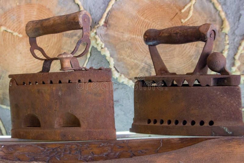 Ferros oxidados velhos na prateleira Ferramentas domésticas retros Ferros do vintage Ferros de alisamento oxidados foto de stock royalty free