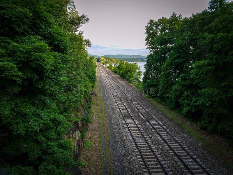 Ferrovia che passa attraverso la foresta alle colline ed al cielo fotografia stock libera da diritti