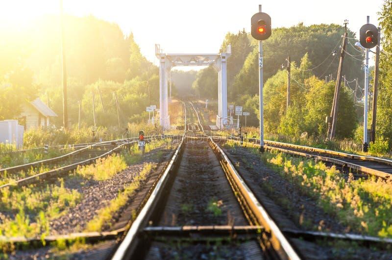 Ferrovia contro il bello cielo al tramonto Paesaggio rurale con la stazione ferroviaria fotografia stock libera da diritti