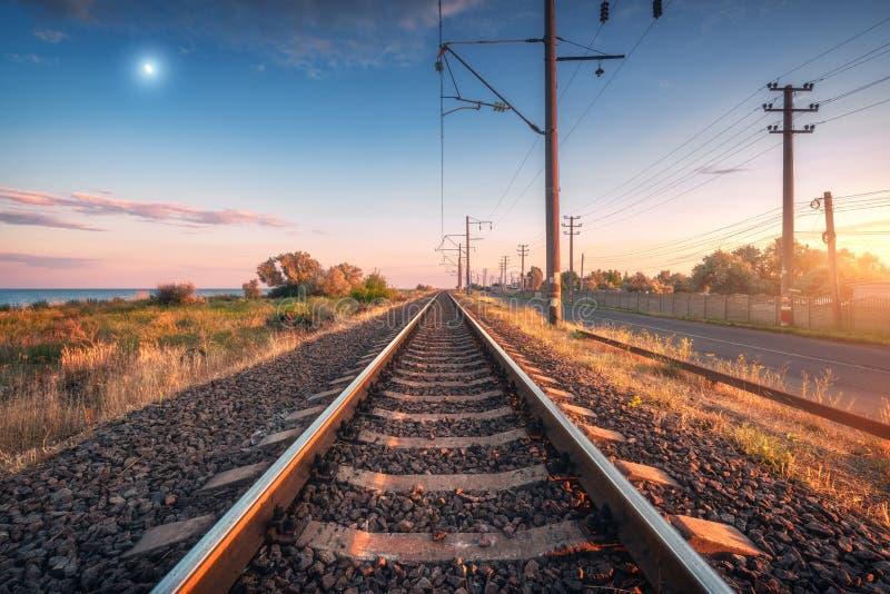 Ferrovia e cielo blu con la luna al tramonto di estate immagini stock libere da diritti