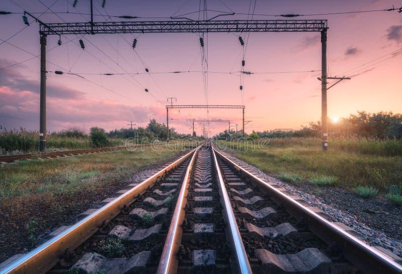 Ferrovia e cielo rosa al tramonto di estate Paesaggio industriale fotografia stock