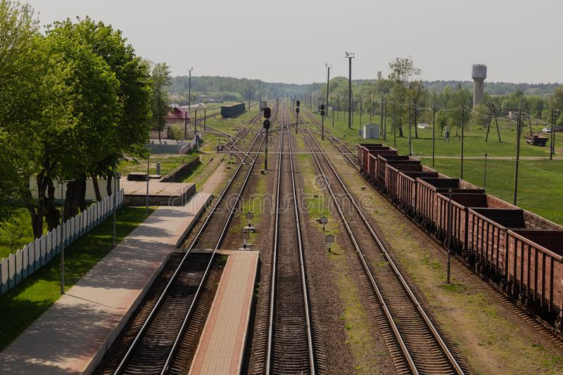 Ferrovia nel moto al tramonto Stazione ferroviaria con effetto contro cielo blu variopinto, concetto industriale del mosso immagini stock