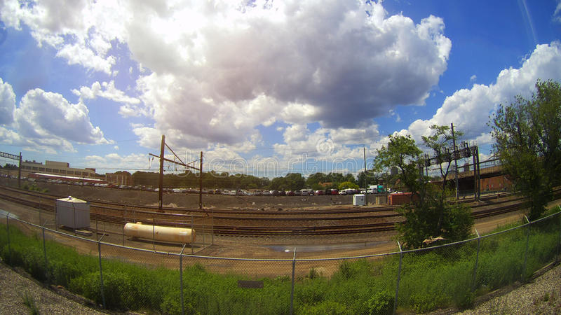 Ferrovia nel moto al tramonto Stazione ferroviaria con effetto del mosso contro cielo blu variopinto fotografia stock libera da diritti