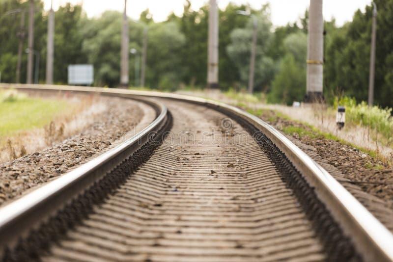 Ferrovia nel moto al tramonto Stazione ferroviaria con effetto del mosso, fondo industriale di concetto fotografia stock