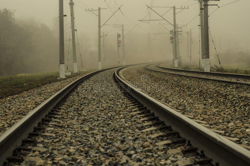 Ferrovia per il treno elettrico Un giro regolare che entra in nebbia fotografia stock