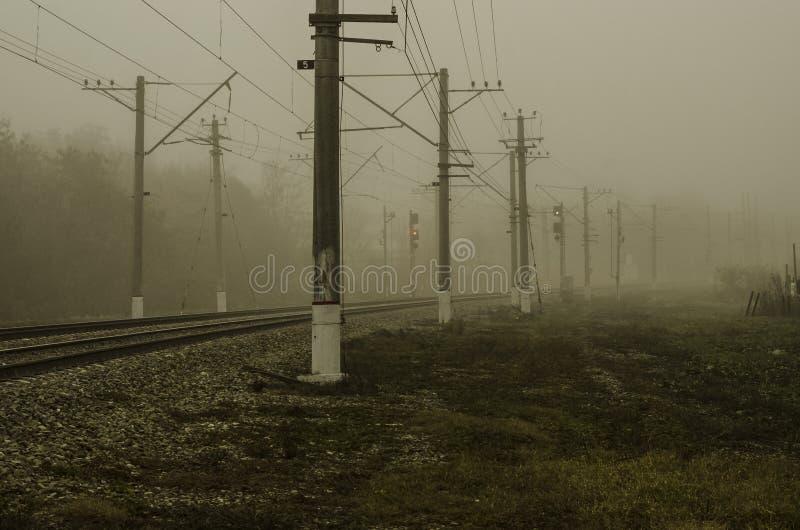 Ferrovia per il treno elettrico Un giro regolare che entra in nebbia immagini stock libere da diritti