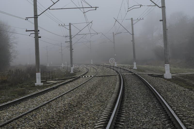 Ferrovia per il treno elettrico Un giro regolare che entra in nebbia fotografia stock libera da diritti