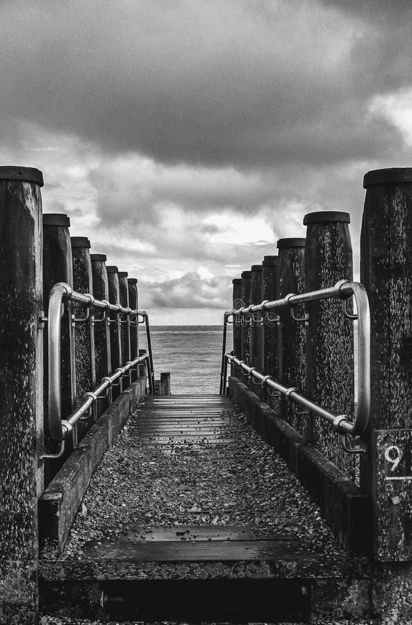 Ferrovie e scalini Eastbourne Beach Sussex bianco e nero fotografia stock libera da diritti